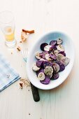 Potato salad made with purple and white potatoes served with a pretzel and beer
