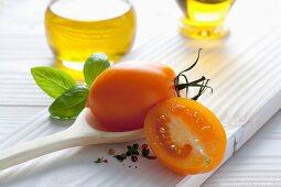 An orange tomato on a wooden spoon