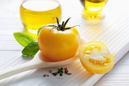 A yellow tomato on a wooden spoon