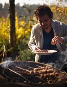 A man grilling venison skewers at an autumn picnic in a forest