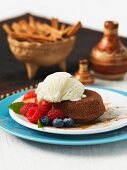 A mini chocolate cake with cinnamon, vanilla ice cream and fresh berries