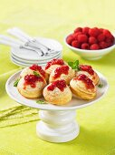 Sponge cakes with raspberry sauce on a cake stand