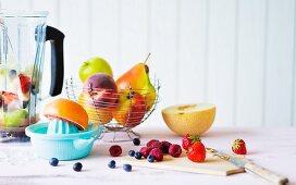 An arrangement of various fruits, a juicer and a blender