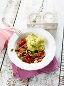 Fried steak and cherry tomatoes served with mashed potatoes and avocado