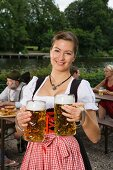 A traditionally dressed German woman with two tankards of beer