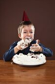 A boy smeared with cream eating cake with his hands