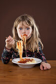 A little girl smeared with tomato sauce eating spaghetti