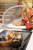 A table with a built in fire pit and a wicker chair on a terrace