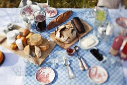 A cheese platter, bread and crockery on a garden table
