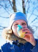 A woman drinking hot lemonade at a winter picnic