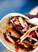 A wrap with grilled sausage, onions and peppers for a winter picnic