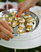 Hands taking pear and cheese canapés with walnuts