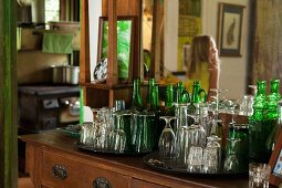 Drinking glasses & glass bottles on antique dressing table with mirror