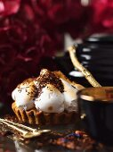 A vanilla tartlet topped with meringue and grated chocolate
