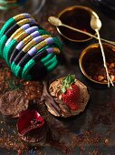 A chocolate cupcake with chocolate cream and strawberries