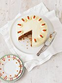 Carrot cake on a cake plate with a large slice cut out of it