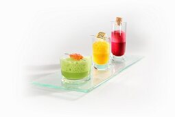 A trio of foam soups with corresponding fish