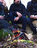 Three men sitting by a campfire in winter