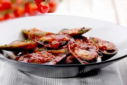 Mussels with tomato sauce on a black plate