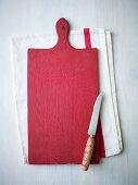 Rotes Schneidebrett aus Holz und Messer auf Geschirrtuch