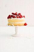 A birthday cream cake with raspberries