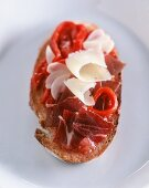 A slice of toasted bread topped with pata negra and manchego cheese