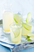 Apple and ginger lemonade in glasses and a carafe