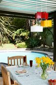 Old baking tins in different colours as pendent lamps hanging above a patio table with a pool in the background