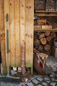 Alter Besen an Holzwand lehnend vor Holzlager und Kisten im Regal