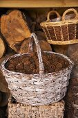 A rustic wicker basket filled with pine cones in front of a wood shed