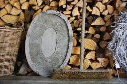 An old broom and a metal tray on a wooden bench in front of a wood pile