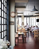An industrial-style loft restaurant with diners in the background