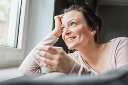A middle aged brunette woman holding a cup of coffee and looking out of a window