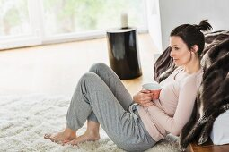 A middle-aged brunette woman sitting on the floor in the living room holding a cup of coffee
