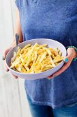 A woman holding a bowl of yellow beans with buttered crumbs