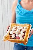 A puff pastry tart with almond cream, nectarines, cherries and meringue
