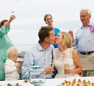 Couple kissing and making a toast with group of friends
