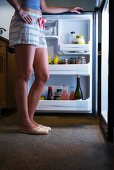 Young woman wearing pyjama shorts standing in front of an open fridge