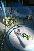 A table laid in blue and white and decorated with flowers