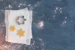 Unbaked star-shaped biscuits and a star-shaped cutter on a piece of parchment paper