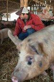 A farmer in a pig pen