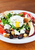 Rocket salad with a poached egg, figs, feta cheese, apples and tomatoes