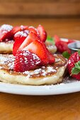 Pancakes with icing sugar and strawberries
