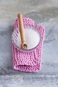 A bowl of salt and a wooden spoon on a knitted pot holder