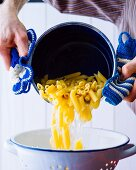 Pasta being drained into a colander