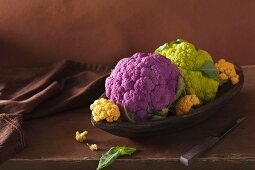 Various different coloured cauliflower in a wooden dish