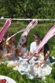 Bunting made from ribbons of colourful fabric remnants on cord in garden; family on lawn in background