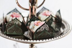 Chocolate confectionery in elegant paper cases decorated with roses and golden sugar pearls