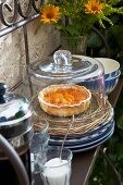 An apricot tart on a wicker plate under a glass cloche with a jug of coffee and French country house crockery on an iron shelf