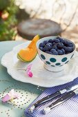 Blueberries in a spotted bowl and a wedge of honeydew melon with antique cutlery on a bistro table in a garden